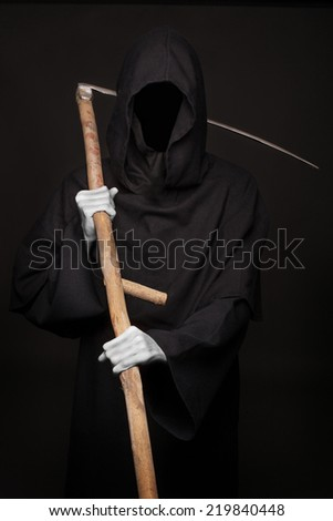 death with scythe standing in the dark. Studio portrait on black background  - stock photo