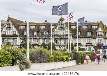 DEAUVILLE - JULY 18: A pedestrian walks past Normandy Barriere hotel on July 18, 2012, Deauville, France. 5 star hotel has 290 rooms and was constructed in 1913 and is famous for half-timbering decor.