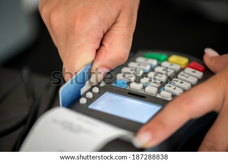 Debit card swiping on pos terminal - stock photo