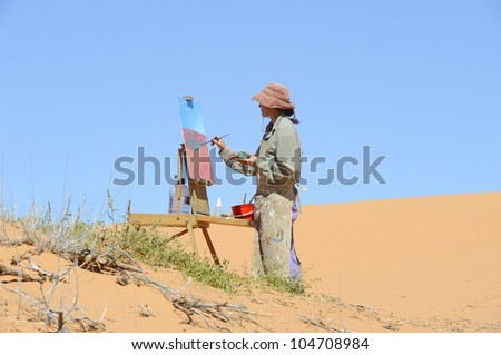 Debra Hilditch, landscape painter at work on location in the Kalahari desert,South Africa