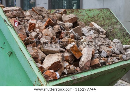 Debris in a green metal container. Broken bricks from the demolition of the building.  - stock photo