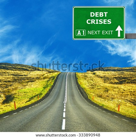 DEBT CRISES road sign against clear blue sky