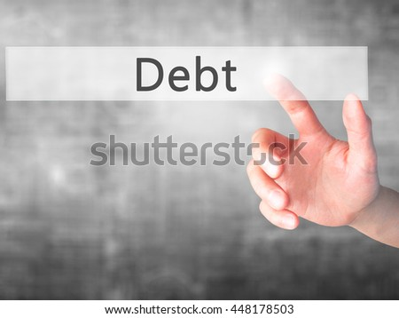 Debt - Hand pressing a button on blurred background concept . Business, technology, internet concept. Stock Photo