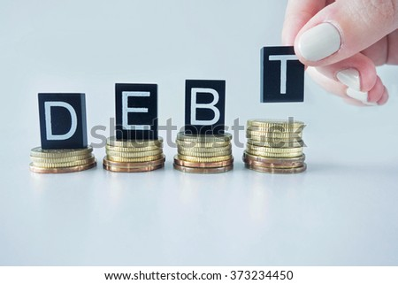 Debt text stacked on coins with cool image temperature  - stock photo