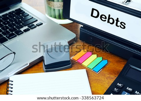 Debts - Office Folder on Office Desktop with Office Supplies. Business Concept on Toned and Blurred Background - stock photo