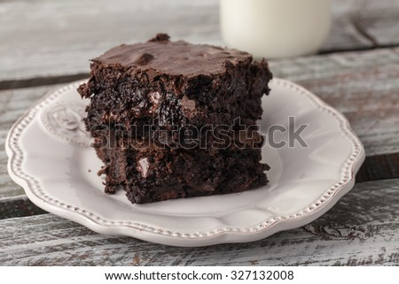 decadent dark chocolate chip brownie with a milk jug - stock photo