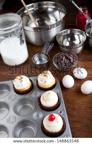 Decadent gourmet cupcakes frosted with a variety of frosting flavors as well as some baking ingredients.  - stock photo
