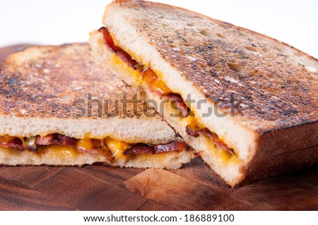 decadent grilled cheese and bacon sandwiches with oozing cheese running out - stock photo
