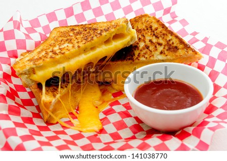 decadent grilled cheese sandwiches with oozing cheese running out with ketchup for dipping - stock photo