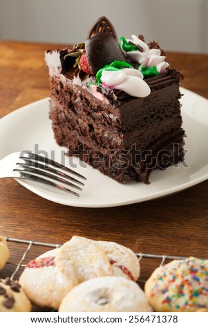 Decadent slice of chocolate cake with iced flowers and chocolate covered strawberries on a plate with a fork. - stock photo
