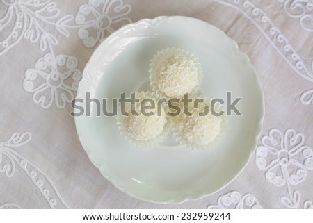 Decadent white chocolate and coconut candies from overhead position - stock photo