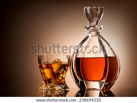 Decanter and glass of golden whiskey on brown background - stock photo