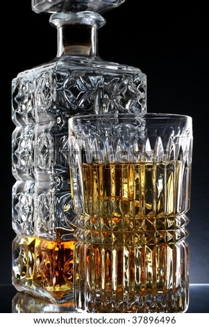 Decanter and glass of whiskey and ice against black background. - stock photo