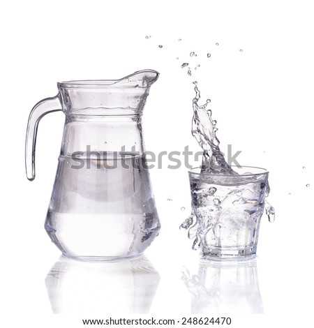 Decanter and water splash in a glass isolated on white - stock photo