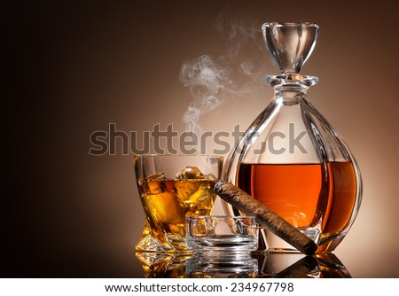 Decanter of whiskey with cigar and glass - stock photo