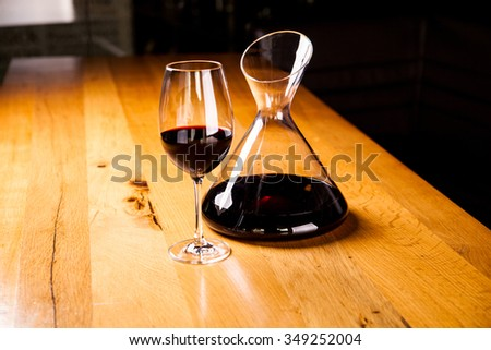 Decanter with red wine and glass on wooden table