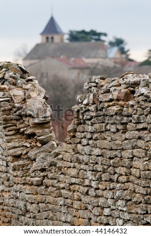 Decayed ancient stone wall constructed around old vineyard and village in Burgundy, France. - stock photo
