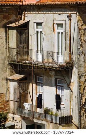 Decayed building wall and balconies of poor neighborhood, Lisbon, Portugal