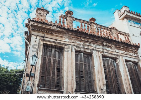 Decayed facade on old building with damaged shutters beside street lamp under beautiful blue partly cloudy sky - stock photo