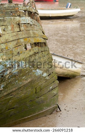 Decaying and rotting wooden boat on River Taw, Fremington, Devon, England - stock photo
