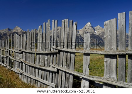 Decaying fence along Mormon Row with the Grand Teton mountains in the background - stock photo