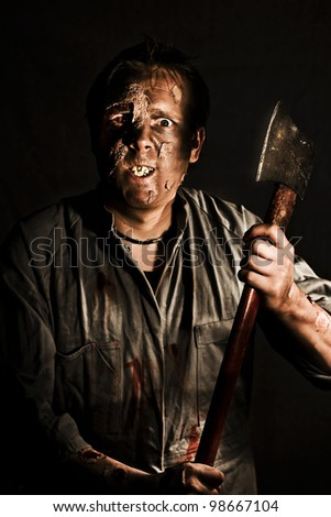 Decaying reanimated zombie corpse with staring eyes emerges from the shadows wielding a large sharp axe as he seeks a victim to kill - stock photo