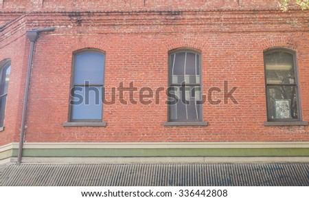 Decaying Red Brick Building.  Red brick building in need of repair with arched windows and drain pipe, for use as an advertising background. - stock photo