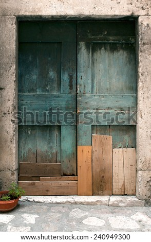 decaying turquoise door mended with planks - stock photo