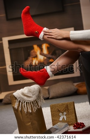 December: female legs in santa claus socks at christmas in front of fireplace. Gifts on the floor. - stock photo