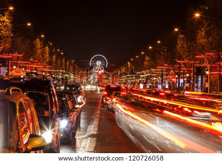 December illumination and traffic lights on the Avenue des Champs-��?lys���©es in Paris,Europe. In the distance you can see the Ferry wheel located in Place de la Concorde. - stock photo
