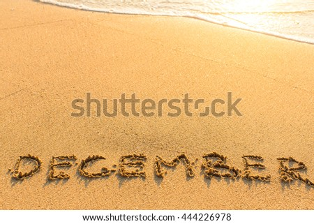 December - inscription on sand beach with the soft wave. - stock photo