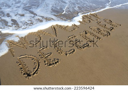 December is coming concept - inscription November and December written on a sandy beach, the wave is starting to cover the word November. - stock photo