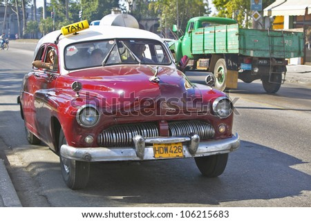 DECEMBER 2004 - Old red taxi driving through the streets of Havana Cuba