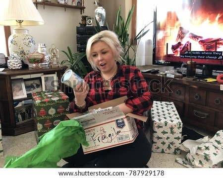 DECEMBER 25 2017 - SCANDIA, MN: A blonde adult female opens a Christmas gift of a Starbucks coffee mug and is surprised. Concept for gift giving and family holiday traditions.