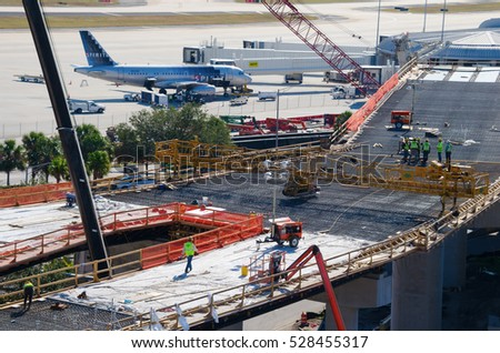 December 2, 2016 - Tampa, Florida, USA: New building expansion construction work at Tampa International Airport with Spirit Airlines plane at loading jetway walkway in background.