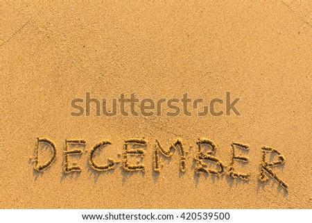 December - word inscription on the gold sand sea beach.  - stock photo