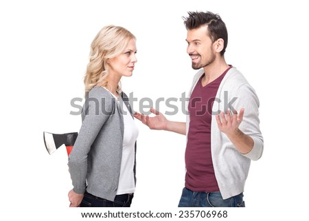 Deception. Conflict. Young couple, man is smiling and woman holding ax behind. White background.