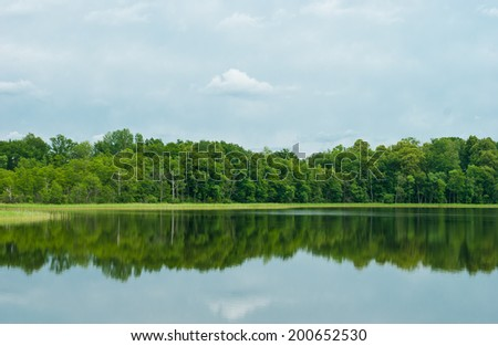Deciduous forest is reflected in a water smooth surface of the lake. Latgale (Latvia) - stock photo