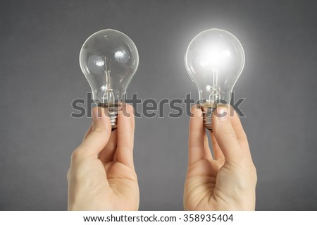 Decision making concept. Hands holding two light bulbs, one of them is glowing - stock photo