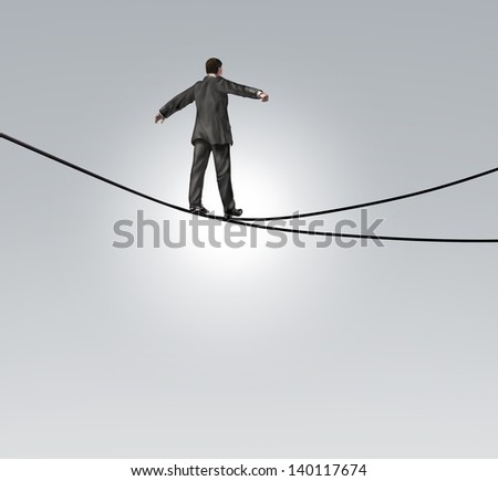 Decision risk and risky choice concept with a businessman maintaining balance walking a high tightrope or tightwire that is split in two opposite directions as a difficult and dangerous dilemma. - stock photo