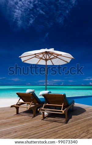Deck chairs and infinity pool over blue tropical lagoon - stock photo