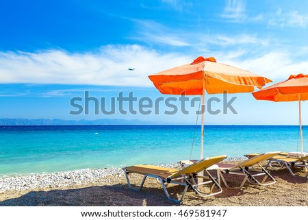 deck chairs and umbrella on background of sea  pebbles