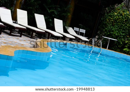 Deck chairs next to a swimming pool.