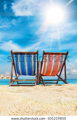 Deck chairs on the beach in Pangan, Thailand