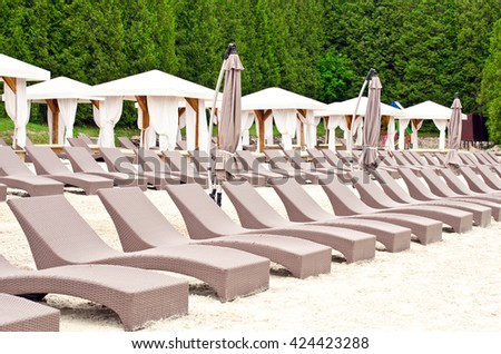 Deck chairs on the sunny sandy beach - stock photo