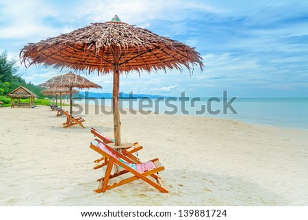 Deck chairs on tropical beach in Thailand - stock photo