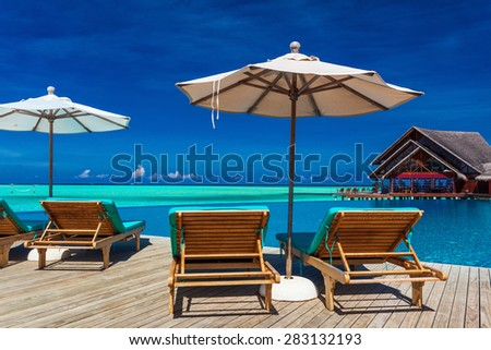Deck chairs with umbrella overlooking infinity pool and tropical lagoon, Maldives
