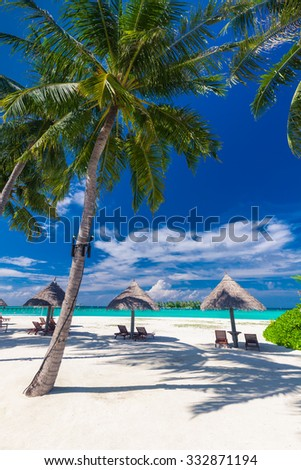 Deck chairs with umbrellas and palm tree on a tropical beach - stock photo