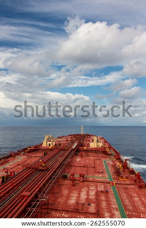 Deck of oil carrier ship under blue cloudy sky. - stock photo