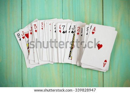 Deck of playing cards on blue wooden background